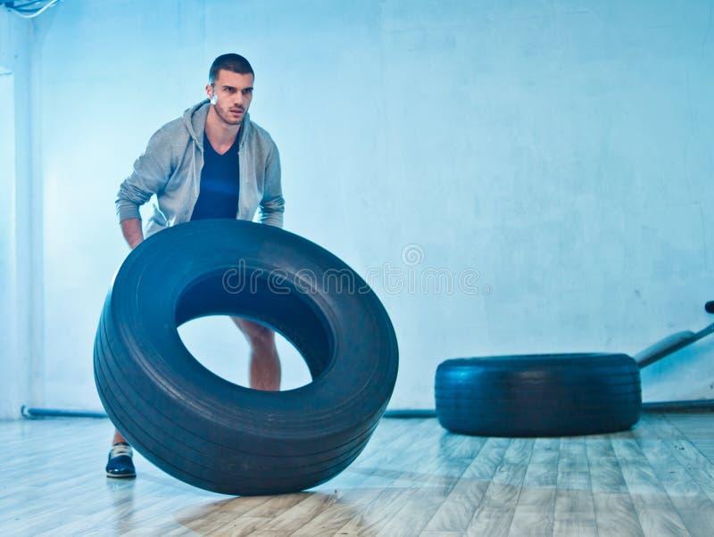 El hombre joven de los deportes aumenta una rueda grande del peso imagen de archivo libre de regalías