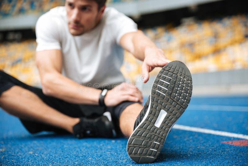 El hombre joven de los deportes en el estadio hace estirar ejercicios fotos de archivo