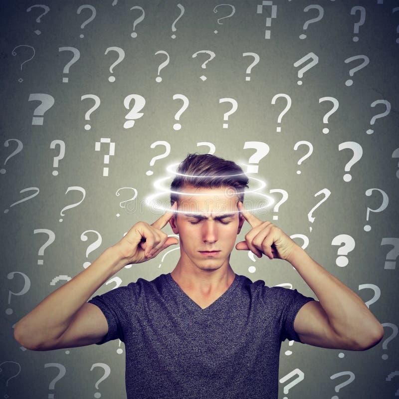 El hombre joven de pensamiento confundido retrato con vértigos del vértigo tiene muchas preguntas Expresión del rostro humano foto de archivo libre de regalías