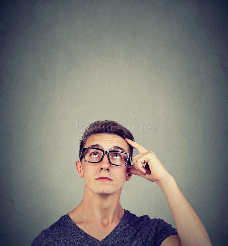 El hombre joven de pensamiento dudoso que rasguña su cabeza busca una solución que mira para arriba foto de archivo