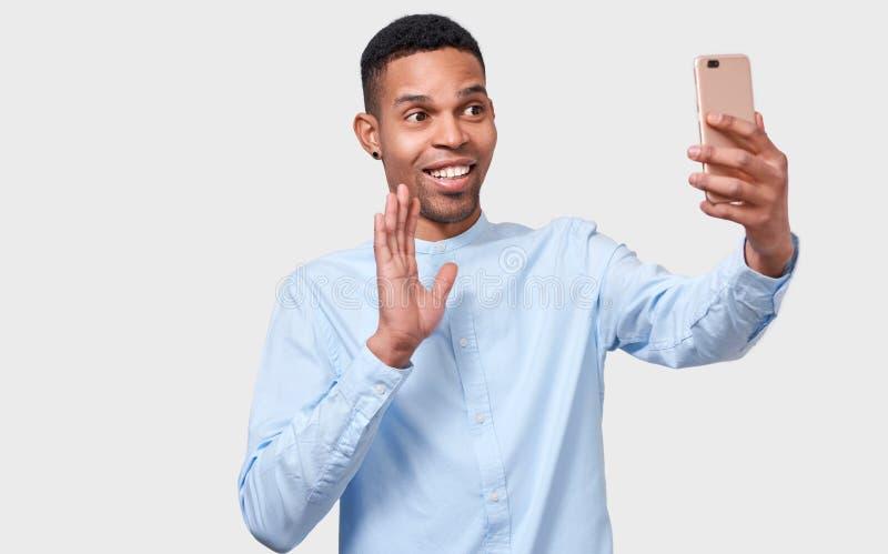 El hombre joven del afroamericano feliz joven sostiene el teléfono elegante moderno, hablando en línea y blogueando foto de archivo