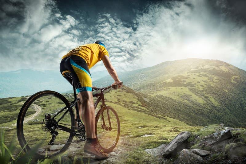El hombre joven del ajuste en el casco que conquista las montañas en una bicicleta foto de archivo