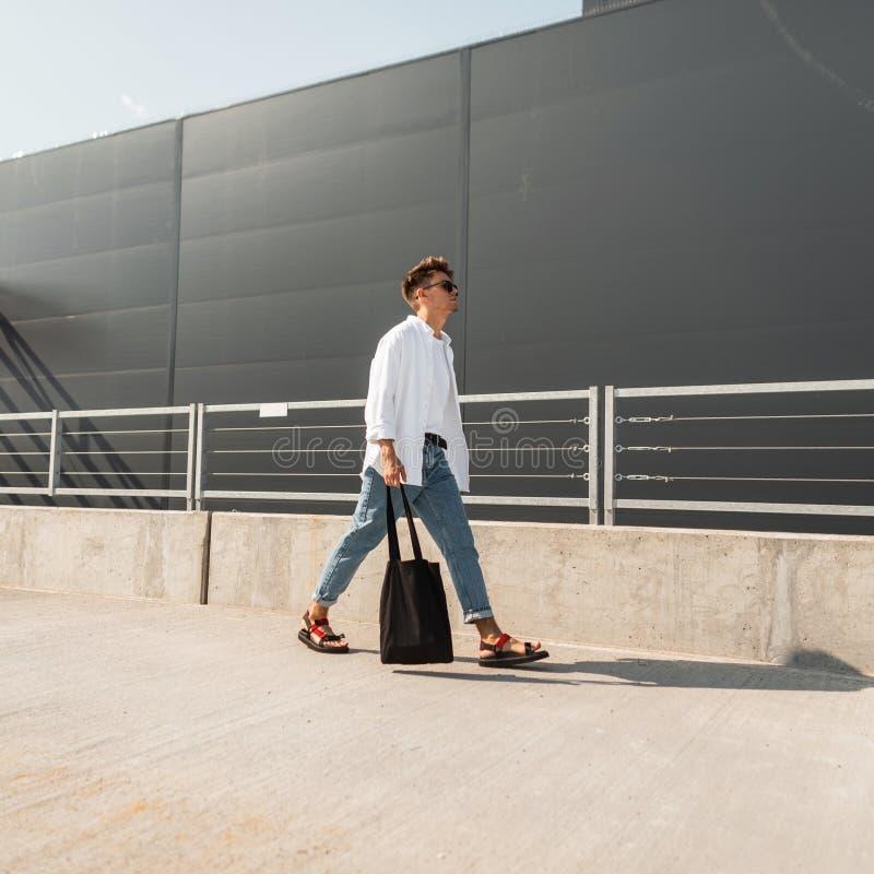 El hombre joven del inconformista de moda en gafas de sol en ropa de moda del verano con el bolso del paño en sandalias del vinta imagenes de archivo