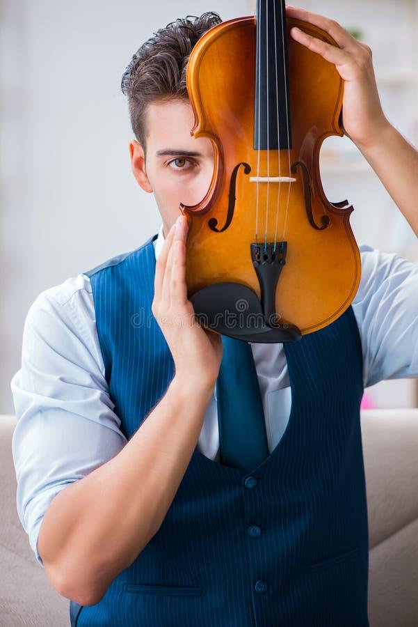 El hombre joven del músico que practica tocando el violín en casa foto de archivo libre de regalías