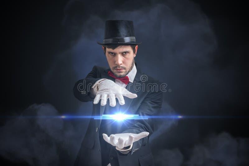 El hombre joven del mago está mostrando la bola brillante que eleva y mantiene flotando Fondo negro imágenes de archivo libres de regalías