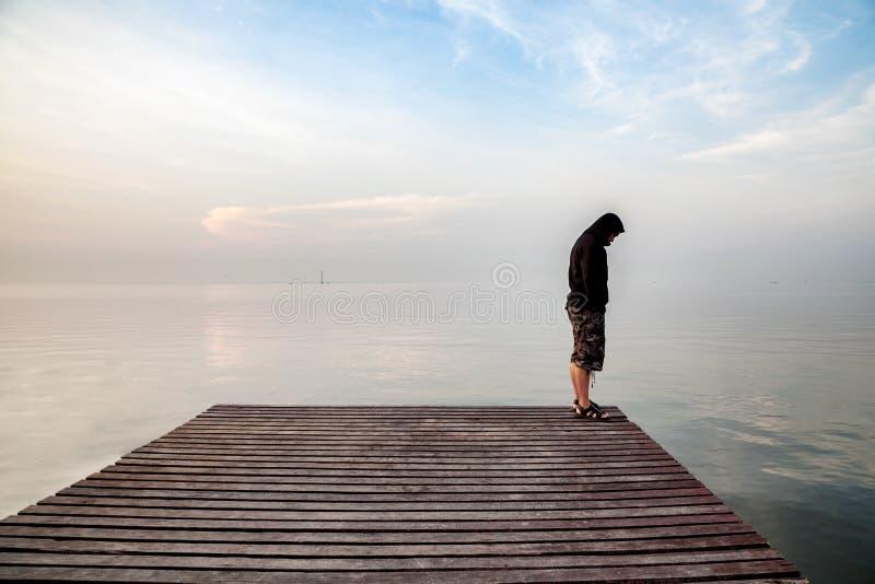 El hombre joven deprimido que llevaba una sudadera con capucha negra que se colocaba en el puente de madera extendió en el mar qu imagen de archivo