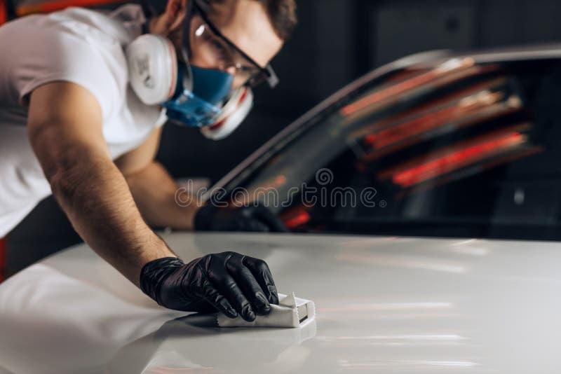 El hombre joven despeja el pulimento un vehículo imágenes de archivo libres de regalías