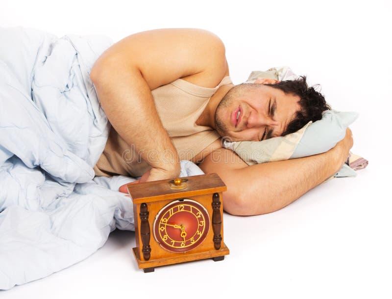 El hombre joven despierta a un reloj de alarma ruidoso fotografía de archivo