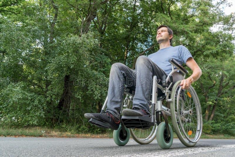 El hombre joven discapacitado o perjudicado se está sentando en la silla de ruedas en naturaleza foto de archivo