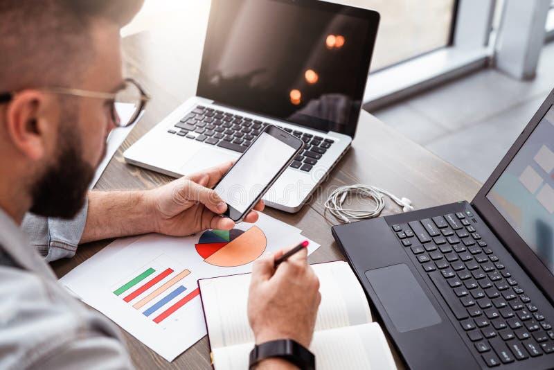 El hombre joven, empresario, freelancer se sienta en oficina en la tabla, utiliza el smartphone, trabajando en el ordenador portá imagen de archivo libre de regalías