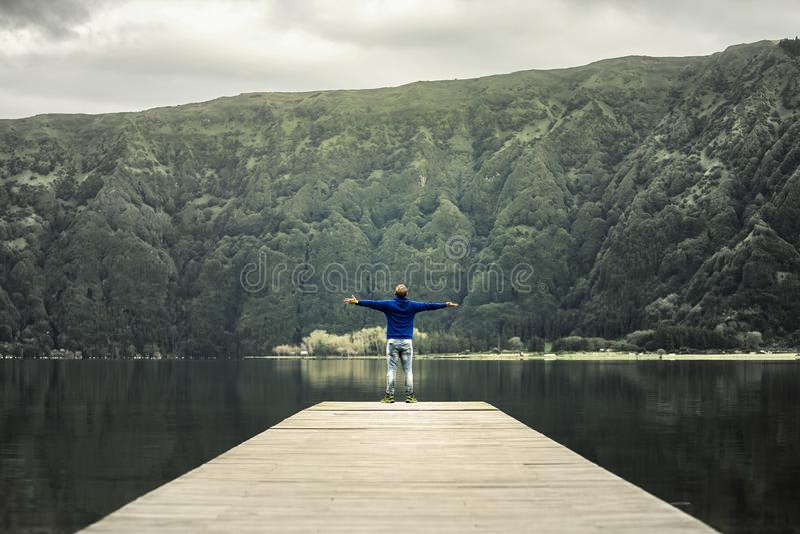 El hombre joven en camiseta azul está defendiendo en el embarcadero el lago volcánico foto de archivo