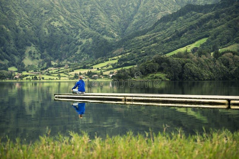 El hombre joven en camiseta azul está defendiendo en el embarcadero el lago volcánico fotos de archivo