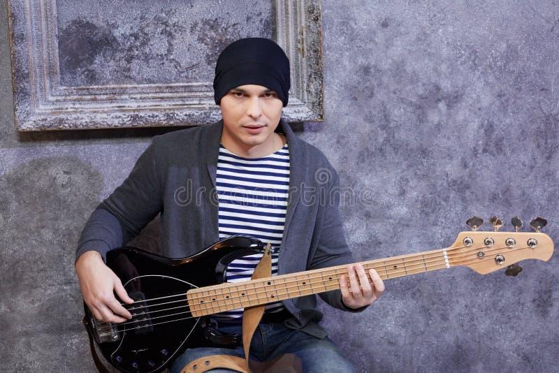 El hombre joven en chaleco rayado y chaqueta hecha punto se sienta con la guitarra fotos de archivo libres de regalías