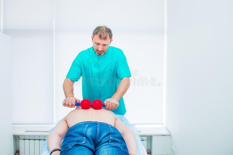 El hombre joven en la fisioterapia que recibe masaje de la bola de quiropráctico del terapeuta A trata la espina dorsal torácica  imagenes de archivo
