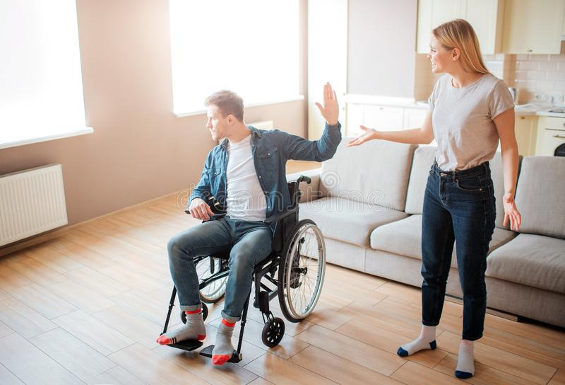 El hombre joven en la silla de ruedas discute con la novia Incapacidad y integraci?n Persona con necesidades especiales Trastorna fotografía de archivo