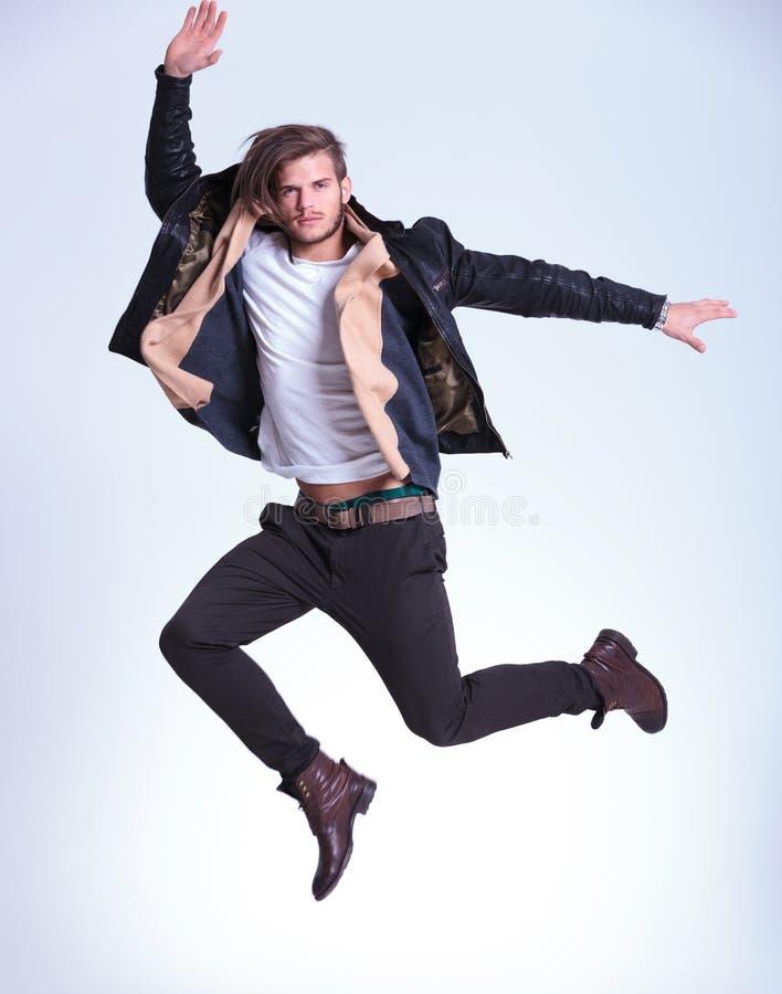 El hombre joven en ropa casual está haciendo un salto de altura fotos de archivo libres de regalías