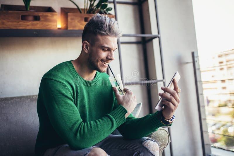 El hombre joven en ropa casual está utilizando una tableta digital imágenes de archivo libres de regalías