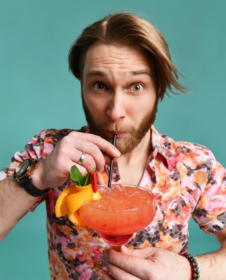 El hombre joven en sombrero y las gafas de sol que beben el cóctel del margarita beben la cámara de mirada feliz del jugo en que  imagen de archivo libre de regalías