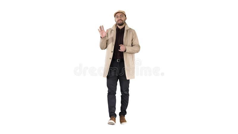 El hombre joven en trenca hace hola gesto en el fondo blanco foto de archivo