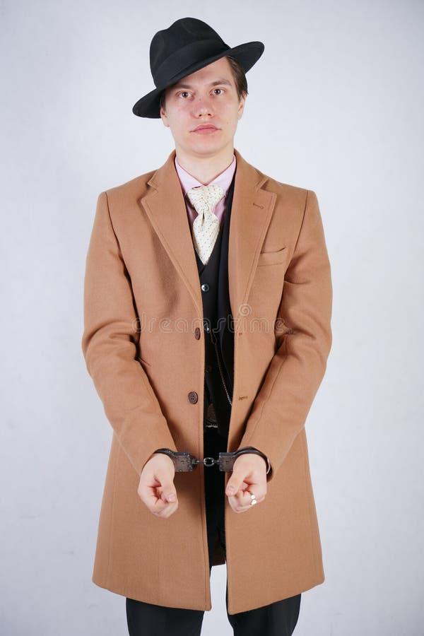 El hombre joven en un traje de negocios negro y una capa beige de la moda con un sombrero elegante se coloca en esposas de la pol fotografía de archivo libre de regalías