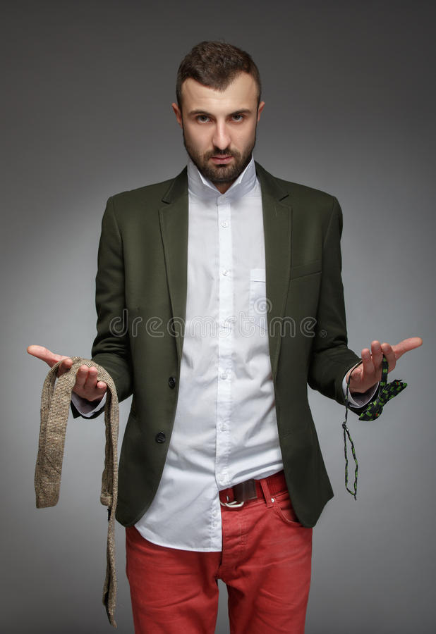 El hombre joven en un traje verde, elige un lazo o una corbata de lazo imagen de archivo libre de regalías