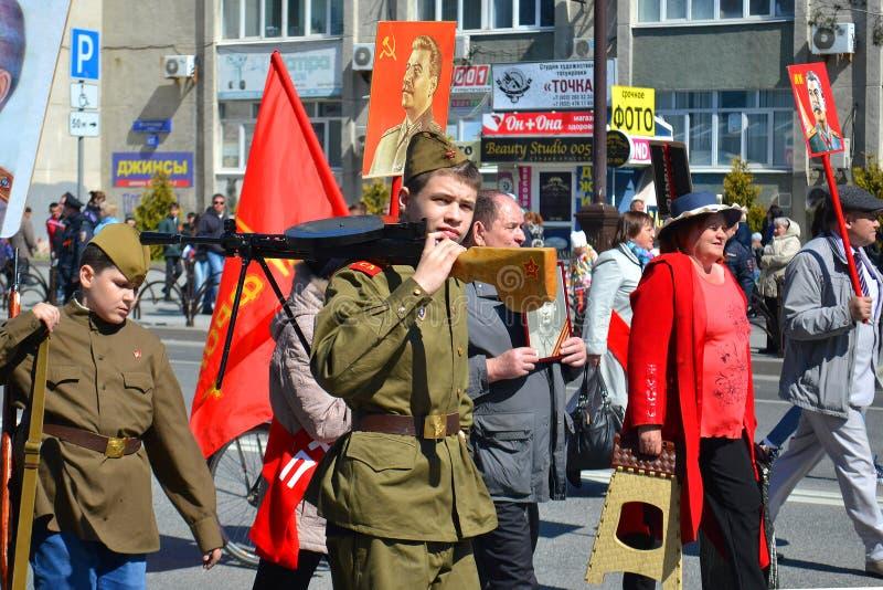 El hombre joven en un uniforme militar con el arma participa adentro imagen de archivo
