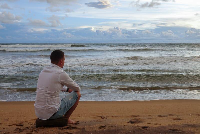 El hombre joven en una camisa blanca resuelve la puesta del sol en una playa tropical del océano imagen de archivo libre de regalías