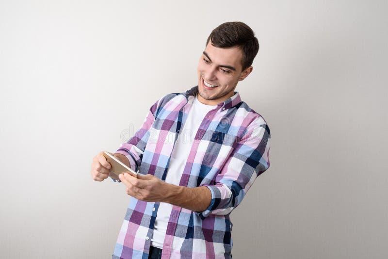 El hombre joven en una camisa de tela escocesa juega con smartphone en el fondo gris fotos de archivo