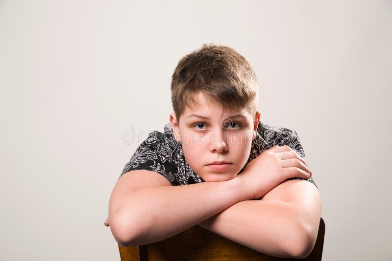 El hombre joven en una camisa negra que se sienta en una silla foto de archivo libre de regalías