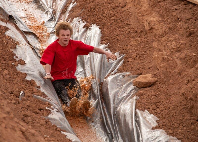 El hombre joven en una camisa roja que resbala abajo de un tobogán acuático en un fango funciona con la carrera de obstáculos imágenes de archivo libres de regalías