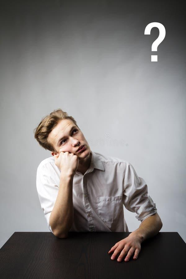 El hombre joven es lleno de dudas y de vacilación Hombre joven y signo de interrogación fotos de archivo