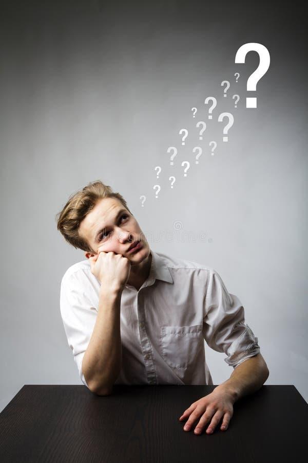 El hombre joven es lleno de dudas y de vacilación Hombre joven y signos de interrogación imagen de archivo
