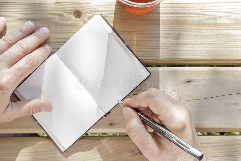 El hombre joven escribe en su cuaderno foto de archivo