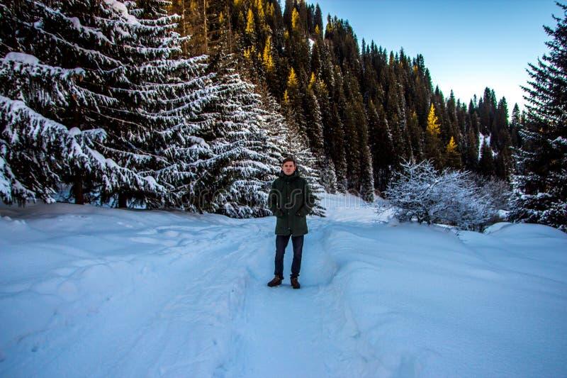El hombre joven está caminando en montañas del invierno fotos de archivo