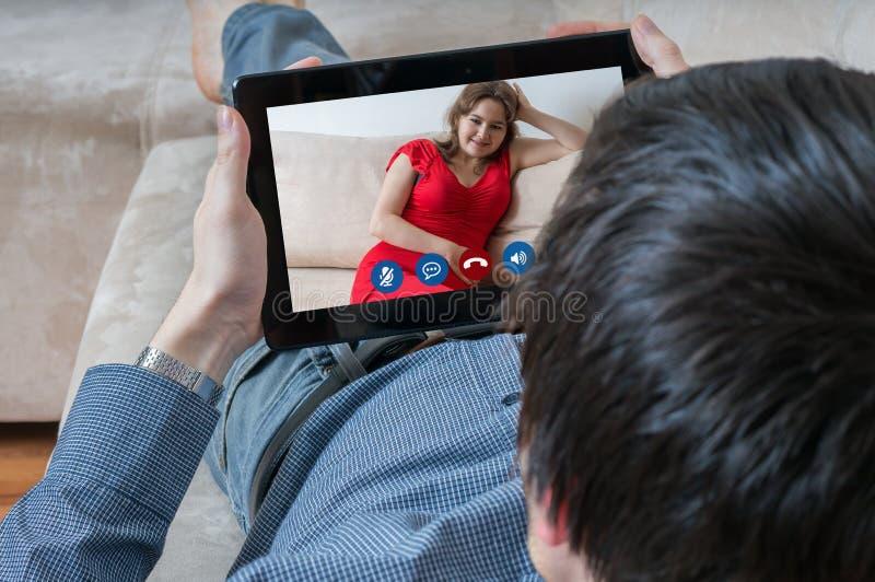 El hombre joven está charlando con su novia Datación y concepto en línea del videochat fotos de archivo