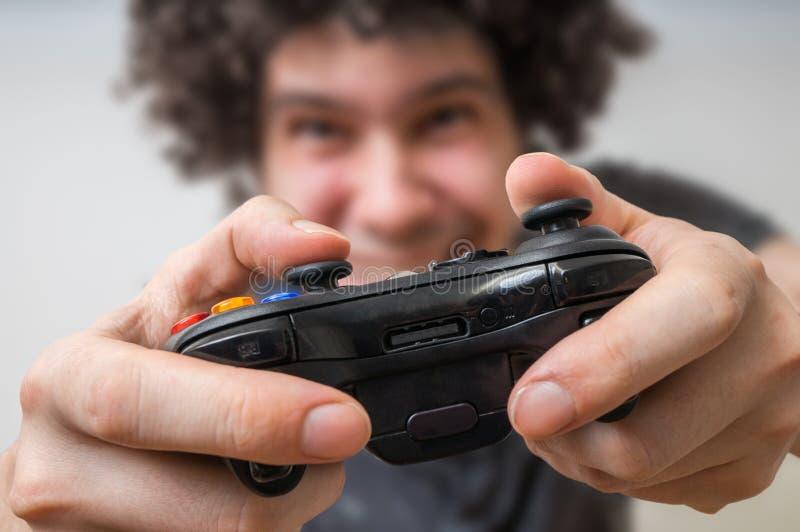 El hombre joven está jugando a los videojuegos y sostiene la palanca de mando o el regulador imagenes de archivo