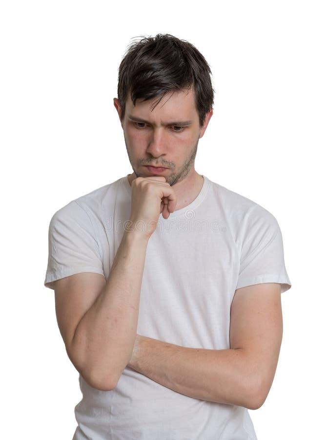 El hombre joven está pensando Aislado en el fondo blanco imagen de archivo libre de regalías