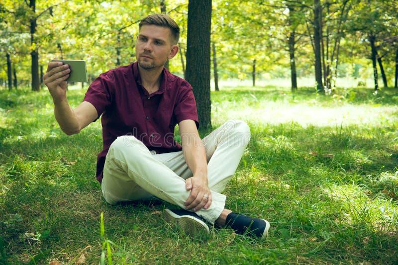 El hombre joven está tomando la foto del selfie con smartphone en el verano p fotografía de archivo libre de regalías