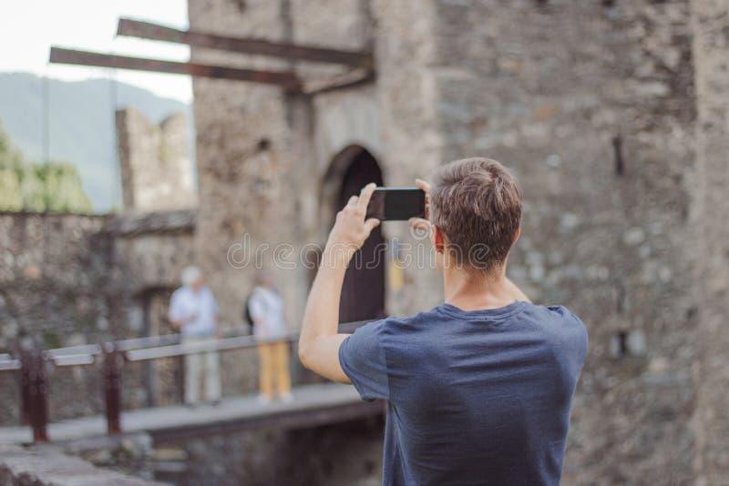 El hombre joven está tomando una imagen de un castillo foto de archivo