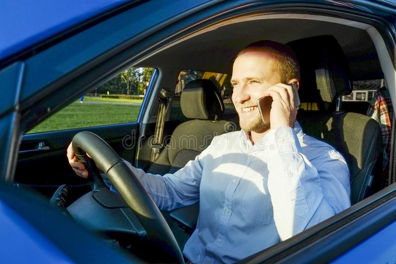 El hombre joven feliz acertado y su coche en puesta del sol suave se encienden en fondo urbanístico Hombre de negocios con el veh imagenes de archivo