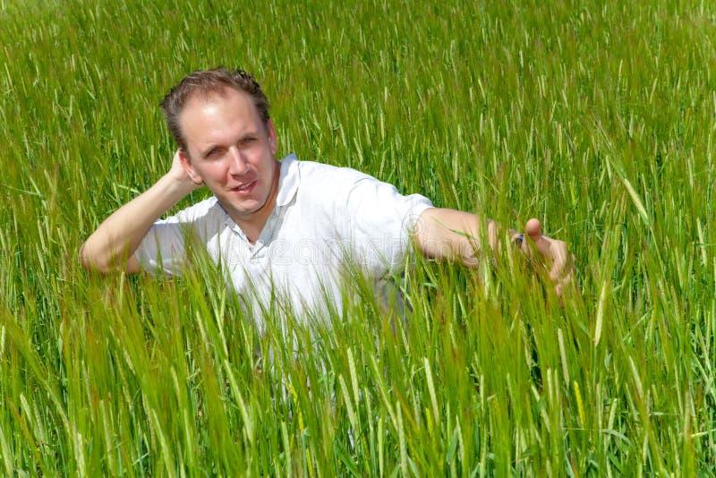 El hombre joven feliz en el campo de oídos verdes. Retrato imágenes de archivo libres de regalías