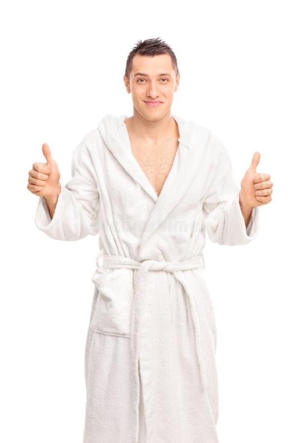 El hombre joven feliz en una albornoz blanca que da dos pulgares para arriba aísla foto de archivo libre de regalías