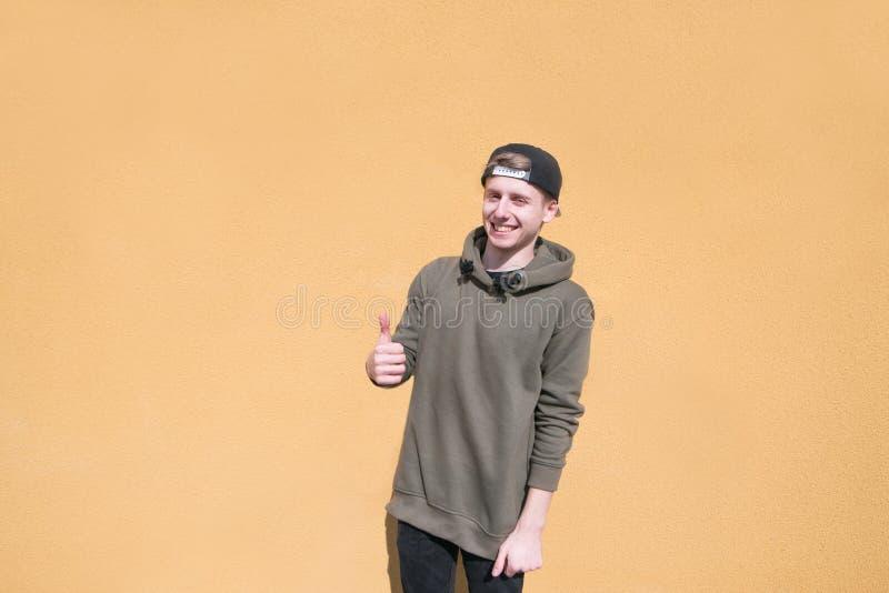 El hombre joven feliz se coloca en el fondo de una pared anaranjada, muestra los pulgares para arriba y las sonrisas imagenes de archivo