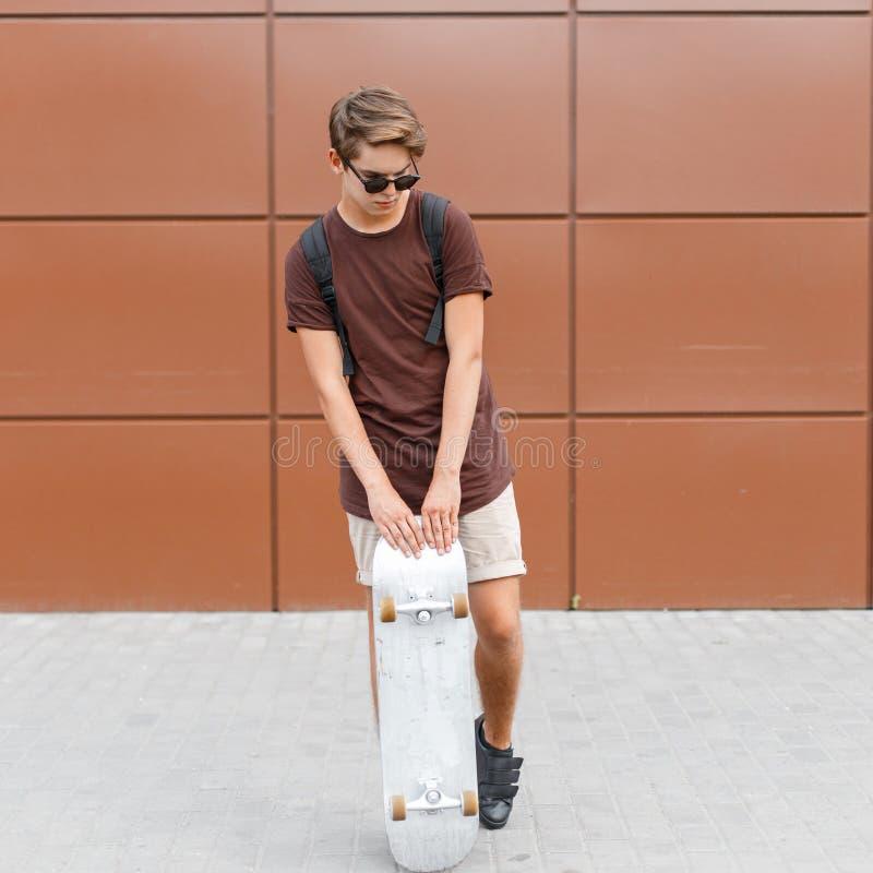 El hombre joven fresco atractivo del inconformista en pantalones cortos en gafas de sol oscuras en una camiseta de moda con una m imagen de archivo libre de regalías