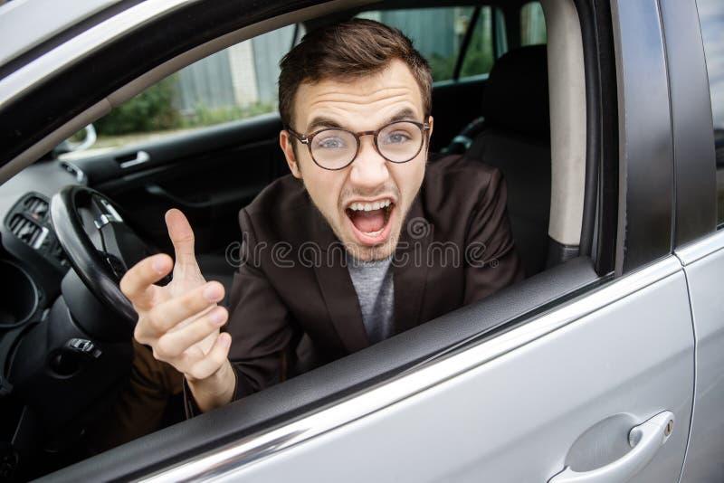 El hombre joven furioso está mirando la cámara mientras que se sienta en su coche Él está gritando en alguien Concepto enojado de fotos de archivo