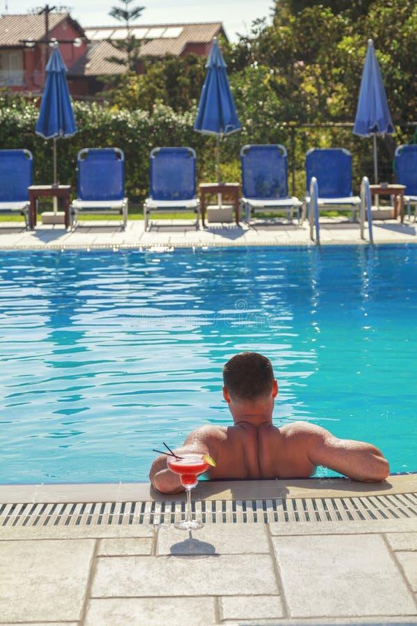 El hombre joven goza en piscina con la bebida del alcohol del cóctel, día de fiesta para relajarse y para tomar el sol fotografía de archivo