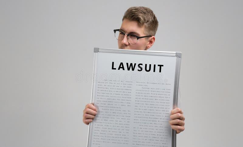 El hombre joven guarda delante de él un cartel con el pleito de la inscripción aislado en un fondo ligero foto de archivo libre de regalías