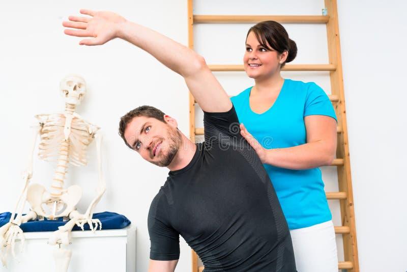 El hombre joven hace estirar ejercicios con el fisioterapeuta imágenes de archivo libres de regalías