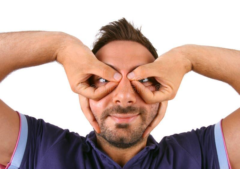 El hombre joven hace una mueca de dolor con sus manos sobre sus ojos fotos de archivo