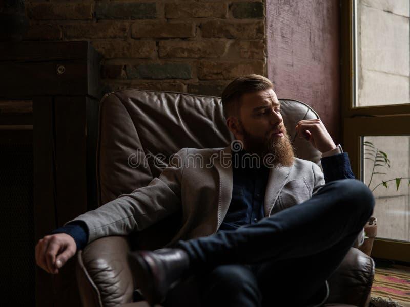 El hombre joven hermoso con la barba está pensando foto de archivo libre de regalías